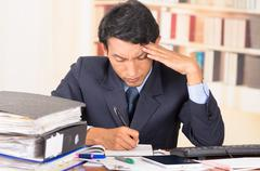 young stressed overwhelmed man with piles of folders on his desk - stock photo