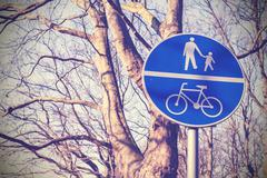 Retro filtered pedestrians and cyclists only sign in a park. Stock Photos