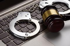 Close-up Of Gavel And Handcuffs On Laptop Stock Photos