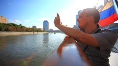 Man taking picture with smartphone on a cruise ship and waving flags. HD Stock Footage