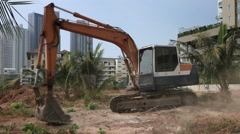 Excavator Digger on a construction site equates land clearing a building site, Stock Footage