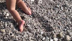 Feet of baby crawling up pebble hill Stock Footage
