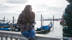 Woman sit on harbor with gondola in background Stock Footage