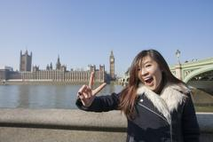 Stock Photo of Portrait of young woman gesturing V-sign against Big Ben at London, England, UK