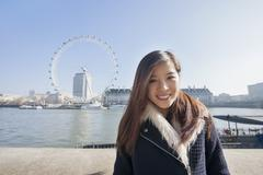 Stock Photo of Portrait of happy young woman standing against London Eye at London, England, UK