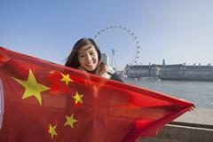 Portrait of happy young woman holding Chinese flag against London Eye at London, - stock photo