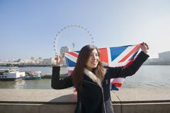 Stock Photo of Happy woman with British flag against London Eye at London, England, UK
