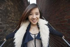 Stock Photo of Portrait of young woman smiling on steps at London, England, UK