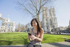Stock Photo of Young woman using cell phone against Westminster Abbey in London, England, UK