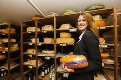 Side view of female salesperson holding cheese in store - stock photo