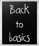 """Back to basics"" handwritten with white chalk on a blackboard Stock Photos"