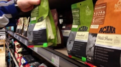 Man buying cat dry food at pet store - stock footage