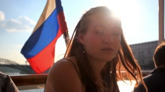 Young attractive woman drinking water on cruise ship at sunlight and flag waving Stock Footage