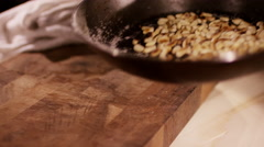 Roasted pine nuts, tossing in a frying pan Stock Footage