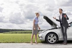 Stock Photo of Full length of business couple having argument by broken car at countryside