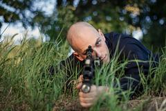 Bold special forces soldier holding a gun in the field Stock Photos