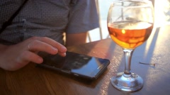 Businessman uses smartphone in sea voyage on cruise ship and drinking glass of Stock Footage