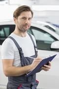 Portrait of confident automobile mechanic writing on clipboard in workshop Stock Photos