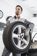 Young maintenance engineer carrying tire in automobile store Stock Photos