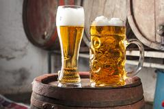 Two Beers with foam and old wood barrels in the background Stock Photos