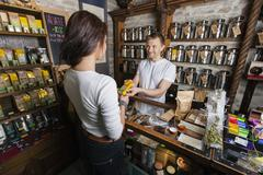Salesperson giving product to female customer in tea store Stock Photos