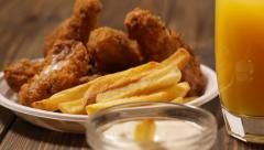 Crisp crunchy golden chicken wings with chips - stock footage