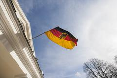 Stock Photo of Low angle view of German flag on government building against cloudy sky,