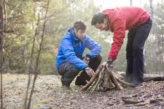 Male hikers arranging firewood in forest - stock photo