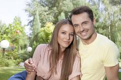 Portrait of beautiful young couple spending leisure time in park - stock photo