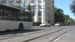Public transportation bus and two cars drive in the city in summer sunny day - stock footage