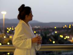 Young, attractive woman in bathrobe drinking red wine and relaxing NTSC Stock Footage
