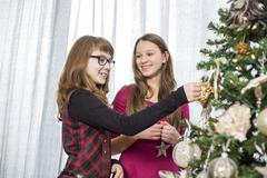 Stock Photo of Sisters decorating on Christmas tree at home