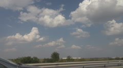 Great white cloudscape over the highway, speeding on empty road, side shooting Stock Footage