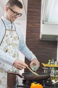 Happy man adding white wine to saucepan while cooking in kitchen Stock Photos