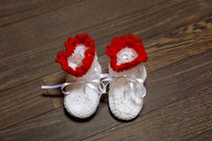 baby's bootee on wooden background - stock photo
