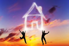 A couple jump and make a house symbol of light. New home, mortgage. Kuvituskuvat