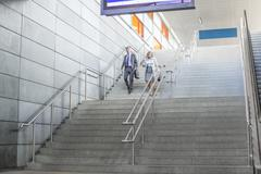 Full length of businessman and businesswoman walk down stairs at railway station Kuvituskuvat