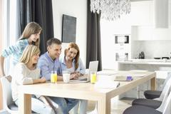 Happy family of four using laptop at home Stock Photos