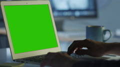 Programmer is Working in Office on Laptop with Green Screen for Mock-up Stock Footage