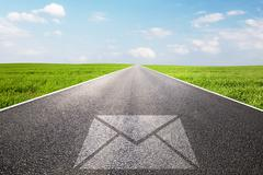 Mail, message symbol on long straight road, highway. Stock Photos