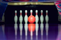 Bowling. Ball is going to hit skittles in the alley. Stock Photos