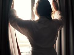 Woman in bathrobe unveil curtains in room in the morning NTSC Stock Footage