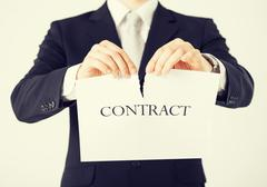 Stock Photo of man hands tearing contract paper