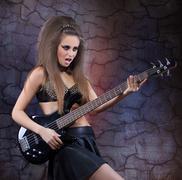 Woman playing music on a bass guitar Kuvituskuvat