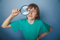 European-looking boy of ten years a joke, looking through a magn - stock photo