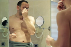Handsome man applying anti wrinkle roll-on on his face in the bathroom NTSC Stock Footage