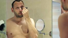 Handsome man applying anti wrinkle roll-on on his face in the bathroom HD Stock Footage