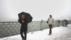 Man with a black umbrella walking in the snow Stock Footage