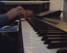 Man plays synthesizer keyboard, sampler, composing  the end of a song - stock footage