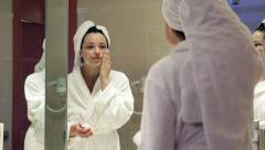 Pretty woman in bathrobe applying beauty cream on her face in the bathroom  HD Stock Footage